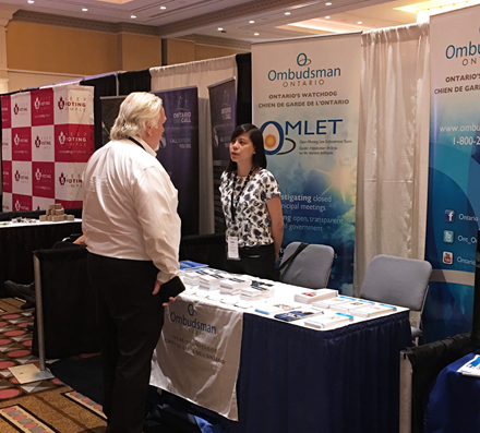 A conference attendee visiting the Ombudsman Ontario booth during the Association of Municipalities of Ontario conference.